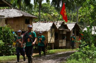 In this photo taken on December 26, 2014, members of the communists' armed wing, the New People's Army (NPA), walk past a hammer and sickle flag displayed in a village as they mark the 46th anniversary of its founding, on the southern island of Mindanao. The Philippine government and communist rebels said on December 26 that formal negotiations to end a lengthy insurgency could restart shortly, though the rebels' armed wing announced it was beefing up its guerilla campaign.   AFP PHOTO / AFP PHOTO / STR