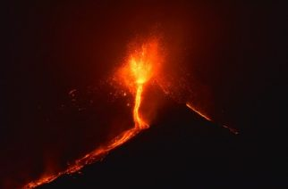 "Lava flows from the Mount Etna volcano on the southern Italian island of Sicily, near Catania, late on December 6, 2015. The volcano on the Mediterranean island threw up an ash column some seven kilometres (4.3 miles) high with lava flowing from the Voragine crater for the first time in two years, the National Institute of Geophysics and Vulcanology (INGV) said. The eruption, which began on December 3, 2015, is among the most ""energetic of the past 20 years,"" added the INGV.  / AFP PHOTO / GIOVANNI ISOLINO"