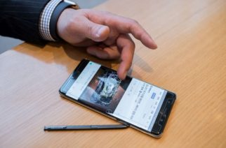 A Samsung customer browses a web page showing a fire-damaged Samsung Note 7 mobile phone, on a similar device, at a Samsung store in a mall beneath the company's headquarters in the Gangnam district of Seoul on October 12, 2016. Samsung Electronics slashed its third-quarter profit estimate by 33.3 percent, citing fallout from the recall nightmare surrounding its scrapped Galaxy Note 7 smartphone. / AFP PHOTO / Ed Jones