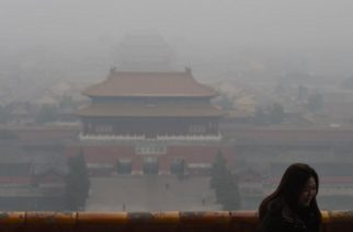 To go with AFP story Climate-warming-UN-COP21-China-environment-economy-law, FOCUS by Benjamin Dooley     In this photo taken on December 8, 2015, a visitor stands in front of the view over the Forbidden City, once the home of China's emperors, on a polluted day in Beijing. In the future, China will shut down a factory before it even pollutes -- or so it hopes, as it deploys big data in the fight against bad air. AFP PHOTO / Greg BAKER / AFP PHOTO / GREG BAKER