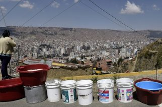 A woman remains next to a line of empty buckets and containers prepared by the inhabitants of a neighbourhood to wait for a water supply tanker, in La Paz on November 23, 2016. Bolivia suffers its worst drought in 25 years. The shortages have sparked protests in various areas, including rural districts whose crops depend on irrigation. / AFP PHOTO / AIZAR RALDES
