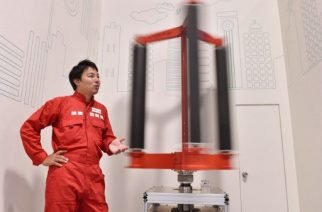 This picture taken on October 20, 2016 shows engineer Atsushi Shimizu, founder and CEO of the Japanese venture company Challenergy, standing next to his bladeless wind turbine in Tokyo. The amount of electricity produced by wind nearly doubled in 2016 from a year earlier, according to a recent survey by the Japan Wind Power Association. But wind power's share of Japan's total energy mix is still less than one percent. / AFP PHOTO / Kazuhiro NOGI / TO GO WITH Japan-energy-environment,FOCUS by Harumi Ozawa