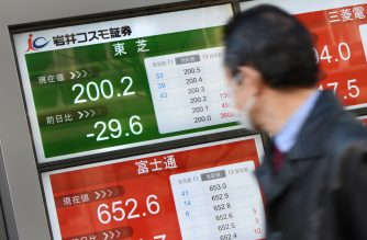 A businessman looks at an electric quotation board flashing the share price of Japan's Toshiba (top/L) in front of a securities company in Tokyo on February 15, 2017.  Toshiba shares tumbled more than 10 percent after the company warning of a 6.2 billion USD writedown in its US nuclear power business, as investors questioned the conglomerate's corporate governance. / AFP PHOTO / TORU YAMANAKA