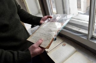 A picture taken on February 27, 2017 shows historian Mikhail Melnichenko, 33, displaying pages from a Soviet-era diary during an AFP interview in Moscow. An enthusiastic group of young Russian historians and volunteers publishes hundreds of never-before-seen Stalin-era diaries on a website called Prozhito, or Lived Through. The site was launched in 2015 and can be searched using the day, author or a keyword. It already includes more than 600 never-published journals. / AFP PHOTO / Natalia KOLESNIKOVA / TO GO WITH AFP STORY BY Anna MALPAS