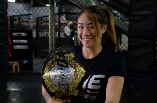 """Singaporean mixed martial art fighter Angela Lee poses with her championship belt during an interview with AFP at a gym in Singapore on March 16, 2017. Top Asian fighter Angela Lee said on March 16 she is prepared to headline a """"new era"""" for women's mixed martial arts in the region, and looked forward to a possible fight in China. / AFP PHOTO / ROSLAN RAHMAN"""