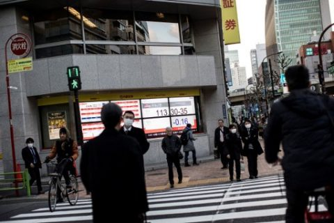 Pedestrians cross a street as an electric quotation board flashes the exchange rate of the Japanese yen against the US dollar in Tokyo on March 17, 2017. Tokyo shares closed slightly higher on March 17 but the gains were capped by a stronger yen after the Federal Reserve hinted at a slower pace of interest rate hikes this year. / AFP PHOTO / Behrouz MEHRI