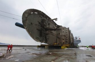 """This handout photo provided and taken on March 26, 2017 by the South Korean Maritime Ministry shows the wreck of the Sewol ferry placed onto a submersible vessel off the coast of the southern South Korean island of Jindo. South Korea's sunken Sewol ferry has been successfully hauled onto a giant heavy lifting ship, officials said on March 25, a step towards returning the vessel to port. / AFP PHOTO / SOUTH KOREAN MARITIME MINISTRY / HANDOUT / RESTRICTED TO EDITORIAL USE - MANDATORY CREDIT """"AFP PHOTO / South Korean Maritime Ministry"""" - NO MARKETING NO ADVERTISING CAMPAIGNS - DISTRIBUTED AS A SERVICE TO CLIENTS"""