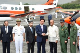 Philippine Defence Minister Delfin Lorenzana (3rd R) shakes hands with his Japanese counterpart Kenji Wakamiya (C) during a handover ceremony of two TC-90 training and maritime surveillance aircraft from the Japan Maritime Self-Defense Force to the Philippine Navy, at a naval base in Sangley point, Cavite province on March 27, 2017. / AFP PHOTO / TED ALJIBE