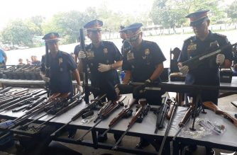 """Officials of the Quezon City Police District present to the media the high-powered firearms and various ammunition recovered from the 36 Tandang Sora compound which was previously illegally occupied by expelled members of the Iglesia Ni Cristo led by Felix Nathaniel """"Angel"""" Manalo.  The QCPD had raided the property and have filed charges against the illegal occupants there.  No bail was recommended for Angel Manalo who had been charged with illegal possession of firearms and ammunition before the Quezon City Prosecutor's Office.   (Eagle News Service)"""