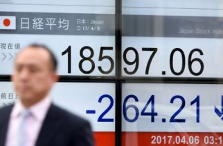 A businessman walks past a stock quotation board flashing the Nikkei 225 key index of the Tokyo Stock Exchange in front of a securities company in Tokyo on April 6, 2017.  Tokyo stocks fell to a four-month low on April 6 after Federal Reserve minutes suggested the US central bank was considering steps that could result in a further tightening of monetary policy. / AFP PHOTO / Toru YAMANAKA