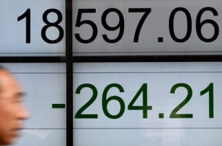 A man walks past a stock quotation board flashing the Nikkei 225 key index of the Tokyo Stock Exchange in front of a securities company in Tokyo on April 6, 2017.  Tokyo stocks fell to a four-month low on April 6 after Federal Reserve minutes suggested the US central bank was considering steps that could result in a further tightening of monetary policy. / AFP PHOTO / Toru YAMANAKA