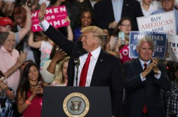 "HARRISBURG, PA - APRIL 29: U.S. President Donald Trump (L) acknowledges supporters as Vice President Mike Pence (R) looks on during a ""Make America Great Again Rally"" at the Pennsylvania Farm Show Complex & Expo Center April 29, 2017 in Harrisburg, Pennsylvania. President Trump held a rally to mark his first 100 days of his presidency.   Alex Wong/Getty Images/AFP"