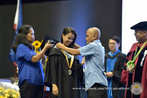 A proud father with his daughter, as he fixes up her medal while the mother waits on to put their daughter's graduation cap.  (Photo courtesy NEU official facebook page)