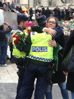 Overflowing of emotion as a woman embraces a policeman at the scene of the Stockholm terror truck attack. (Photo by Fritzie Joy, Eagle News Service)
