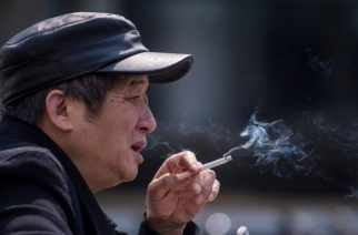 In this photo taken on February 28, 2017, a man smokes a cigarette on the streets in Shanghai.   Shanghai widened its ban on public smoking March 1 as China's biggest city steps up efforts to stub out the massive health threat despite conflicts of interest with the state-owned tobacco industry.  / AFP PHOTO / Johannes EISELE