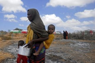 Newly displaced Somali women and children walk to a food distribution at the Kaxda district, outskirts of Mogadishu, on April 9, 2017.   Somalia, a Horn of Africa country of 12 million people, is facing its third famine in 25 years of civil war and anarchy. At least 260,000 people died in the 2011 famine in Somalia -- half of them children under the age of five, according to the UN World Food Program.  / AFP PHOTO / Mohamed ABDIWAHAB