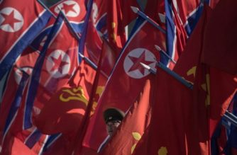 A Korean People's Army (KPA) soldier stands between flags prior to the opening ceremony for the Ryomyong Street housing development in Pyongyang on April 13, 2017. Completion of the sprawling Ryomyong Street development, just down a wide avenue from the mausoleum where Kim Jong-Un's grandfather Kim Il-Sung and father Kim Jong-Il lie in state, was repeatedly promised in time for the 105th anniversary of the birth of the North's founder. / AFP PHOTO / Ed JONES