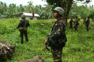 This photo taken on May 10, 2017 shows Philippine soldiers patrolling along a village near a highway in Maguindanao province, in southern island of Mindanao, after almost a week of attacks on members of the Bangsamoro Islamic Freedom Fighters (BIFF). More than 24,000 people fled their homes as the Philippine military used airstrikes and artillery against Muslim extremists who have pledged allegiance to the Islamic State, authorities said May 11.  / AFP PHOTO / FERDINANDH CABRERA