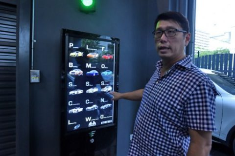 This photograph taken on May 18, 2017 shows used car dealer Gary Hong showing the selection buttons for luxury supercars displayed inside the AutoBahn Motors (ABM) building in Singapore. A vending machine that dispenses luxury cars to well-heeled buyers is the latest space-saving innovation in land-starved Singapore -- just don't try to shake it if it gets stuck. / AFP PHOTO / ROSLAN RAHMAN