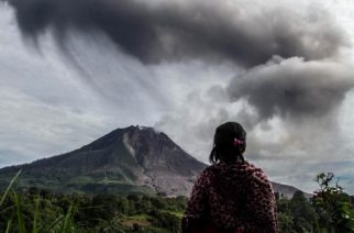A villager looks on as Mount Sinabung volcano spews thick volcanic ash, as seen from Beganding village in Karo, North Sumatra province, on May 19, 2017.  Sinabung roared back to life in 2010 for the first time in 400 years. After another period of inactivity, it erupted once more in 2013 and has remained highly active since. / AFP PHOTO / Ivan DAMANIK