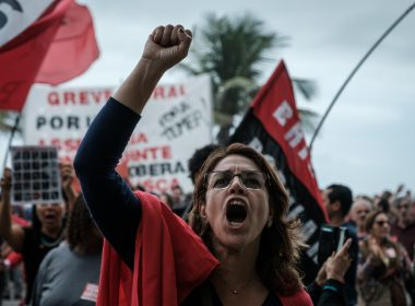"A protester shouts slogans in front of the house of lower house speaker Rodrigo Maia -who would initially take over the presidency if President Michel Temer resigns or is impeached- during a protest against Temer in Rio de Janeiro, Brazil, on May 21, 2017. Maia is one of the many legislators being investigated in the ""Car Wash"" probe, the biggest corruption investigation in Brazil's history. Temer won a reprieve Sunday when a key coalition partner delayed a decision on whether to abandon him over an explosive corruption scandal. / AFP PHOTO / Yasuyoshi Chiba"