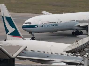 (FILES) In this file photo taken on March 15, 2017 a Cathay Pacific Boeing 777 passenger aircraft (top) taxis past a stationary plane on the tarmac at the international airport in Hong Kong.  Hong Kong's flagship airline Cathay Pacific said on May 22, 2017 it would cut 600 staff as part of a major overhaul to slash costs and repair its bottom line.   / AFP PHOTO / Anthony WALLACE