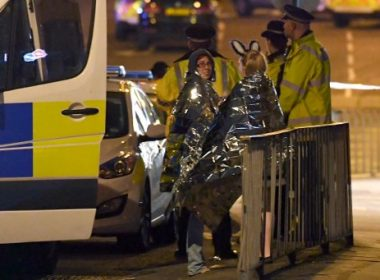 Concert goers wait to be picked up at the scene of a suspected terrorist attack during a pop concert by US star Ariana Grande in Manchester, northwest England on May 23, 2017. The man behind a terror attack at a pop concert in Manchester late Monday died when he detonated his device, killing 22 others including children and injuring 59 people, police said on May 23. / AFP PHOTO / Paul ELLIS / ALTERNATIVE CROP