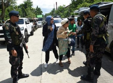 """Philippine policemen check evacuees from Marawi aboard a van at a checkpoint by the entrance of Iligan City, in southern island of Mindanao on May 24, 2017. Philippine President Rodrigo Duterte warned that martial law would be """"harsh"""" and like a dictatorship, after imposing military rule in the south of the country to combat Islamist militants. / AFP PHOTO / TED ALJIBE"""