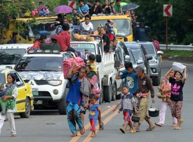 A family carrying their belongings walks in front of other residents in vehicles as they flee from Marawi on the southern island of Mindanao on May 26, 2017, as fighting between Islamist militants and government forces continues. Philippine security forces bombed residential areas in a southern city on May 25 as they battled Islamist militants who were holding hostages and reported to have murdered at least 11 civilians. / AFP PHOTO / Ted ALJIBE