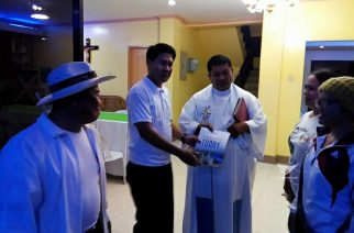 """A Catholic priest receives a copy of the PASUGO or """"God's Message"""" magazine in Mindanao.  (Eagle News Service)"""