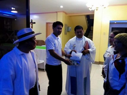 "A Catholic priest receives a copy of the PASUGO or ""God's Message"" magazine in Mindanao.  (Eagle News Service)"