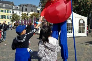 These kids,  hand out pamphlets of the Iglesia Ni Cristo (Church of Christ)  to a man in stilts and a costume in Bonn, Germany during the Europe Day observance.  (Photo by Gemma Tropel, Eagle News Service Germany)