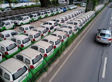 FILE PHOTO: This photo taken on May 22, 2017 shows a car passing new electric vehicles parked in a parking lot under a viaduct in Wuhan, central China's Hubei province. / AFP PHOTO / STR / China OUT