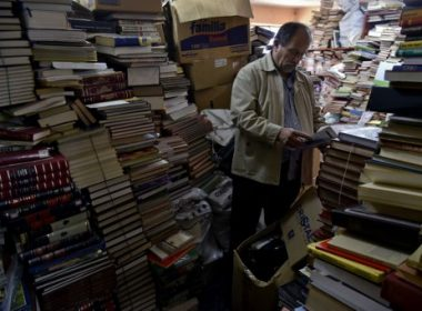 """Jose Alberto Gutierrez checks books stacked in his library on the first floor of his house in Bogota, on May 18, 2017.  Bogota has who rescues its books. For more than two decades Jose Alberto Gutierrez - """"The Lord of Books"""", as he is known in Colombia - drives a garbage truck through the gray and cold streets of Bogota. In addition to wastes, he has collected thousands of books that crowded into his home, converted into a free library. / AFP PHOTO / GUILLERMO LEGARIA"""