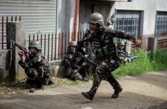 """Philippine Army Scout Rangers take positions during a mission to flush out Islamist militant snipers in Marawi, on the southern island of Mindanao on June 6, 2017. With bomb-proof tunnels, anti-tank weapons hidden in mosques, human shields and a """"mastery"""" of the terrain, Islamist militants holed up in a southern Philippine city are proving a far tougher opponent than military chiefs expected.  / AFP PHOTO / NOEL CELIS"""