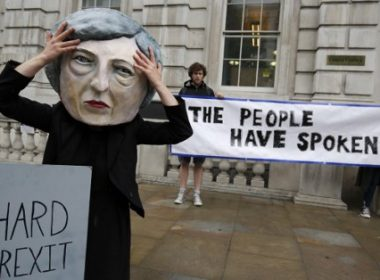 """A demonstrator wears a mask depicting Britain's Prime Minister and leader of the Conservative Party Theresa May, poses with a mock gravestone bearing the words """"Hard Brexit, RIP"""", during a protest photocall near the entrance 10 Downing Street in central London on June 9, 2017 as results from a snap general election show the Conservatives have lost their majority. British Prime Minister Theresa May faced pressure to resign on June 9 after losing her parliamentary majority, plunging the country into uncertainty as Brexit talks loom. The pound fell sharply amid fears the Conservative leader will be unable to form a government and could even be forced out of office after a troubled campaign overshadowed by two terror attacks. / AFP PHOTO / ADRIAN DENNIS"""