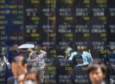 Pedestrians are reflected on a stock quotation board of the Tokyo Stock Exchange in Tokyo on June 14, 2017. Tokyo stocks rose on June 14, tracking another record close for the Dow and S&P 500 on Wall Street, with technology firms bouncing back from recent losses and automakers posting gains.  / AFP PHOTO / Kazuhiro NOGI
