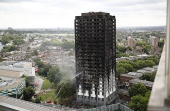 An automated hose sprays water onto Grenfell Tower, a residential tower block in west London that was caught in a huge blaze on June 15, 2017. Firefighters searched for bodies today in a London tower block gutted by a blaze that has already left 12 dead, as questions grew over whether a recent refurbishment contributed to the fire. / AFP PHOTO / Tolga AKMEN