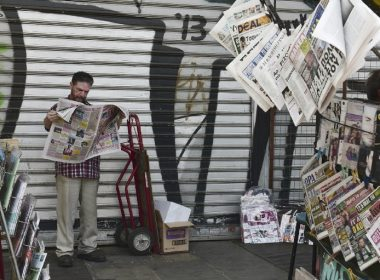 A man reads a newspaper next to a newspaper kiosk in central Athens on June 16, 2017. Eurozone ministers struck a long-delayed bailout deal with Greece on June 15, 2017 to unlock badly needed rescue cash, but warned Athens would have to wait for debt relief. / AFP PHOTO / LOUISA GOULIAMAKI