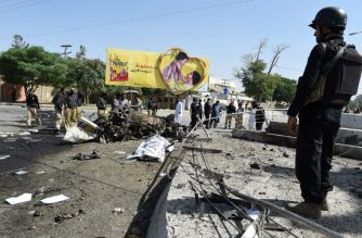 EDITORS NOTE: Graphic content / A body is covered at the site of an explosion as Pakistani security officials stand guard in Quetta on June 23, 2017. An explosion targeting a police vehicle in Pakistan's southwestern Quetta city on June 23 killed at least five people and injured 14 others, officials said. The explosion occurred in front of the office of the police chief in Quetta city, which is capital of the mineral rich southern Balochistan province rife with the separatist and Islamist insurgencies. / AFP PHOTO / BANARAS KHAN