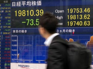 A man walks past a stock quotation board flashing the key Nikkei index of the Tokyo Stock Exchange in front of a securities company in Tokyo on May 15, 2017.  Tokyo stocks opened lower on May 15 with a stronger yen pressuring exporter shares as geopolitical risks linger with North Korea's continued missile tests.   / AFP PHOTO / Kazuhiro NOGI