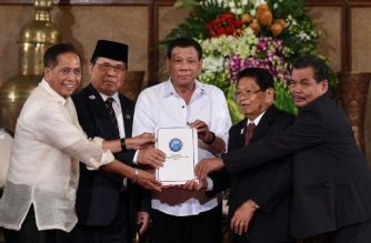 """Philippine President Rodrigo Duterte (C) poses with Secretary of the Peace Process Jesus Dureza (L), Al-Hajj Murad (2nd L), chairman of Moro Islamic Liberation Front (MILF), Ghazali Jaafar (2nd R), vice chairman of MILF and Mohagher Iqbal (R), MILF chief negotiator, as they join hands holding a draft of the Bangsamoro Basic Law (BBL) during a ceremony at the Malacanang Palace in Manila on July 17, 2017. Duterte offered """"genuine autonomy"""" to the Philippines' Muslim minority on July 17 to help him defeat Islamist militants who seized a southern city in the gravest challenge to his year-old rule. / AFP PHOTO / TED ALJIBE"""
