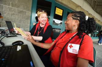 Canadian Red Cross volunteers, Charlie Shymko (L) from Winnipeg, Manitoba, and Vic Parker from Delaware USA wait to assist wildfire evacuees in Kamloops, British Columbia on July 18, 2017. Tens of thousands of Canadians who fled wildfires were unable to return home as the massive blazes raged on. Officials said that 159 fires were still burning, 60 of them out of control, in the western province of British Columbia, where the flames have already consumed 188,000 hectares (464,500 acres) of forest and uncultivated land. / AFP PHOTO / Don MacKinnon