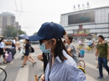 """People cross an intersection on a hazy day in Beijing on July 20, 2017. Chinese cities had fewer """"good air"""" days in the first half of 2017 compared to the same period last year despite government efforts to curb incessant smog, according to official data. / AFP PHOTO / GREG BAKER"""