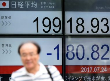 A man walks past a stock quotation board flashing the Nikkei 225 key index of the Tokyo Stock Exchange in front of a securities company in Tokyo on July 24, 2017.  Tokyo stocks opened lower, taking a weak lead from modest declines on Wall Street, while yen strength hurt sentiment. / AFP PHOTO / Toru YAMANAKA