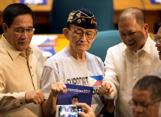 "News in photo:  Former president Ramos does the trademark ""Duterte"" closed fist pose in Congress"