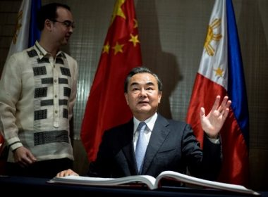 "China's Foreign Minister Wang Yi  (R) waves after signing the guestbook as Philippine Foreign Affairs scretary Alan Peter Cayetano looks on in Manila on July 25, 2017.  China urged Southeast Asian nations on July 25 to unite and ""say no"" to outside forces seeking to interfere in the South China Sea dispute -- an apparent swipe at the United States ahead of a regional summit. China's Foreign Minister Wang Yi made the statement during a two-day visit to Manila where he hailed the ""strong momentum"" in the improvement of bilateral ties under Philippine President Rodrigo Duterte. / AFP PHOTO / NOEL CELIS"