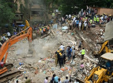 Indian rescue workers look for survivors at the site of a building collapse in Mumbai on July 25, 2017.  Rescuers were frantically searching for up to 40 people feared trapped in a four-storey building that collapsed July 25 in India's financial capital of Mumbai, officials said. / AFP PHOTO / PUNIT PARANJPE