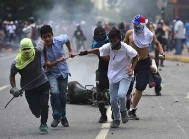 Anti-government activists drag a police motorbike burnt after the explosion of an explosive device during a protest against the elections for a Constituent Assembly in Caracas on July 30, 2017. Deadly violence erupted around the controversial vote, with a candidate to the all-powerful body being elected shot dead and troops firing weapons to clear protesters in Caracas and elsewhere. / AFP PHOTO / Ronaldo SCHEMIDT
