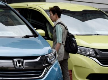 A woman walks beside vehicles from Honda Motor displayed in front of their headquarters in Tokyo on August 1, 2017. Honda was expected later in the day on August 1 to release the company's financial results from April until June for the fiscal year 2017. / AFP PHOTO / Toru YAMANAKA